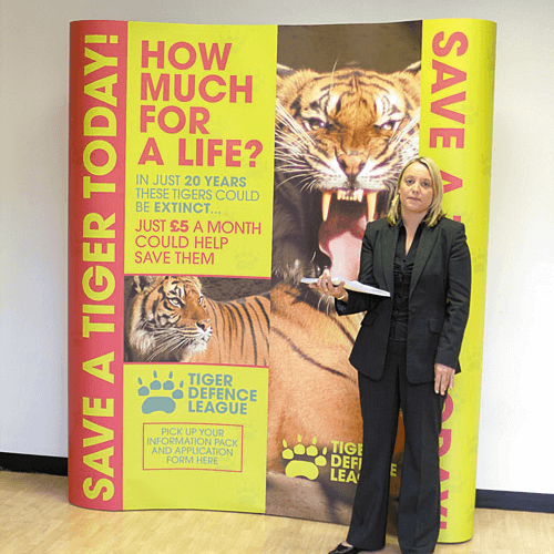 A woman standing beside a Pop-Up Display Poster