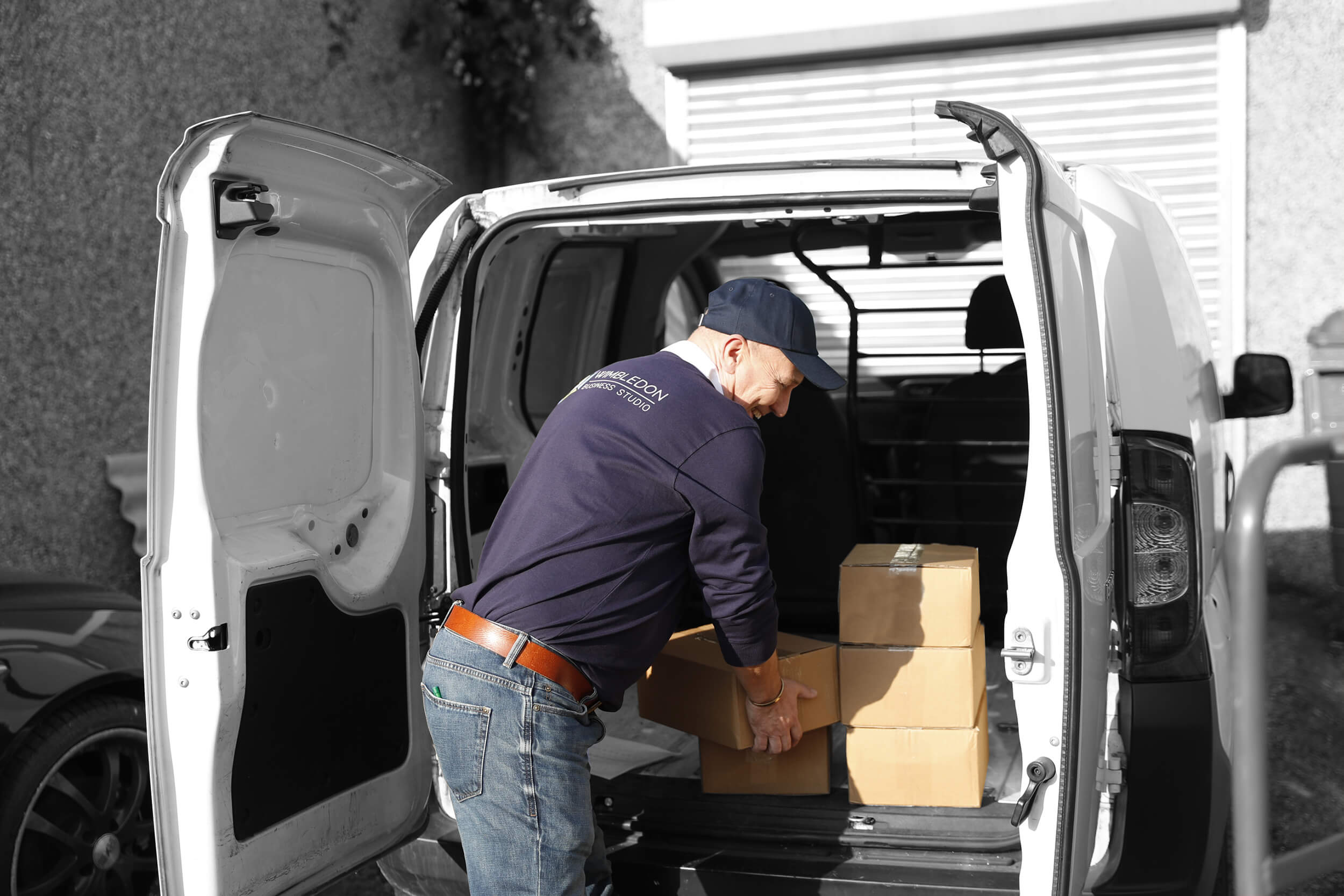 a man unloading boxes at the back of a van